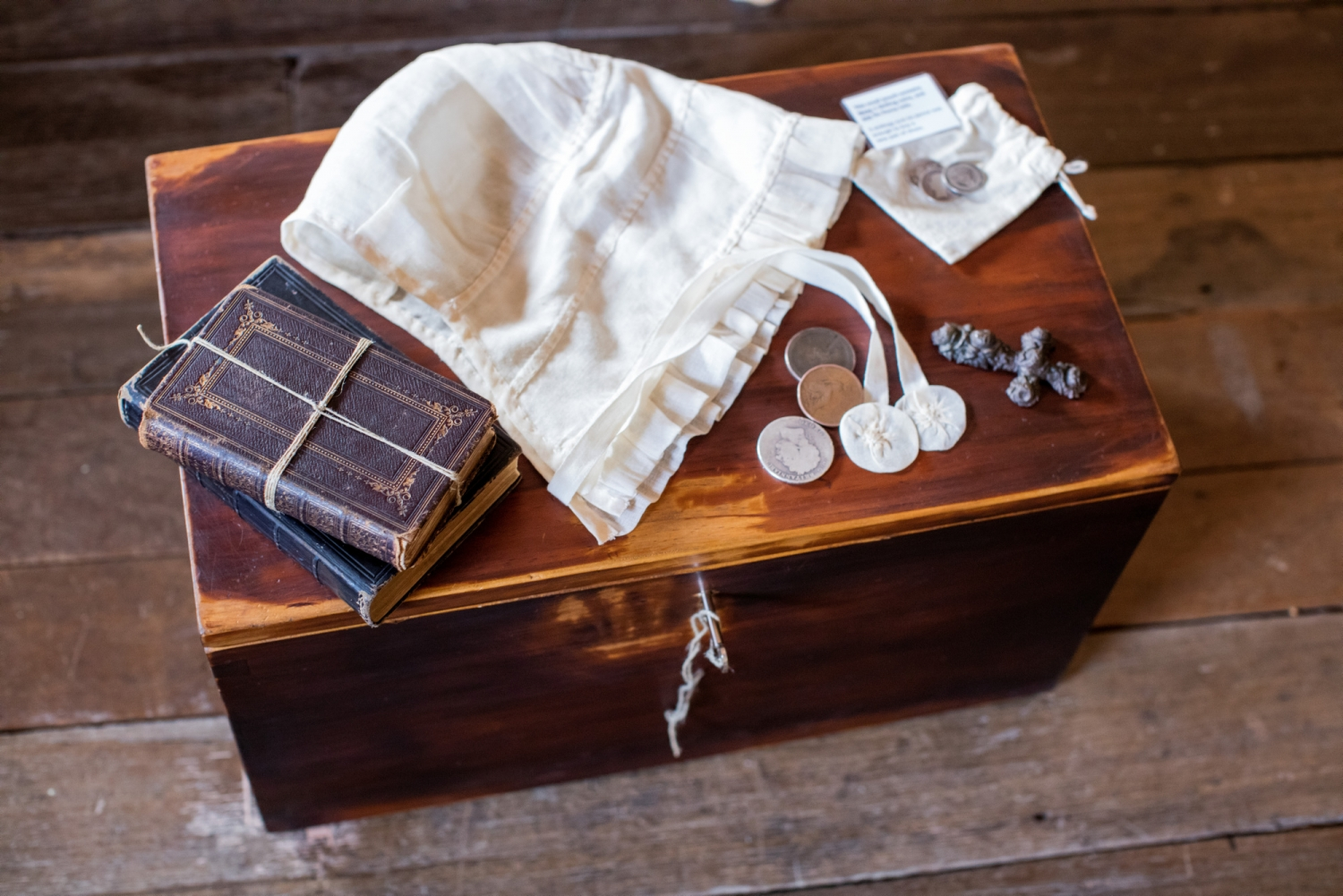 Wooden trunk with selection of clothing set out on top.