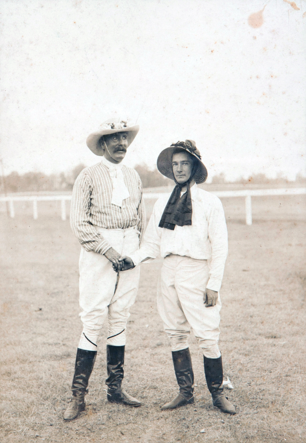 Two men in riding gear and hats on field.