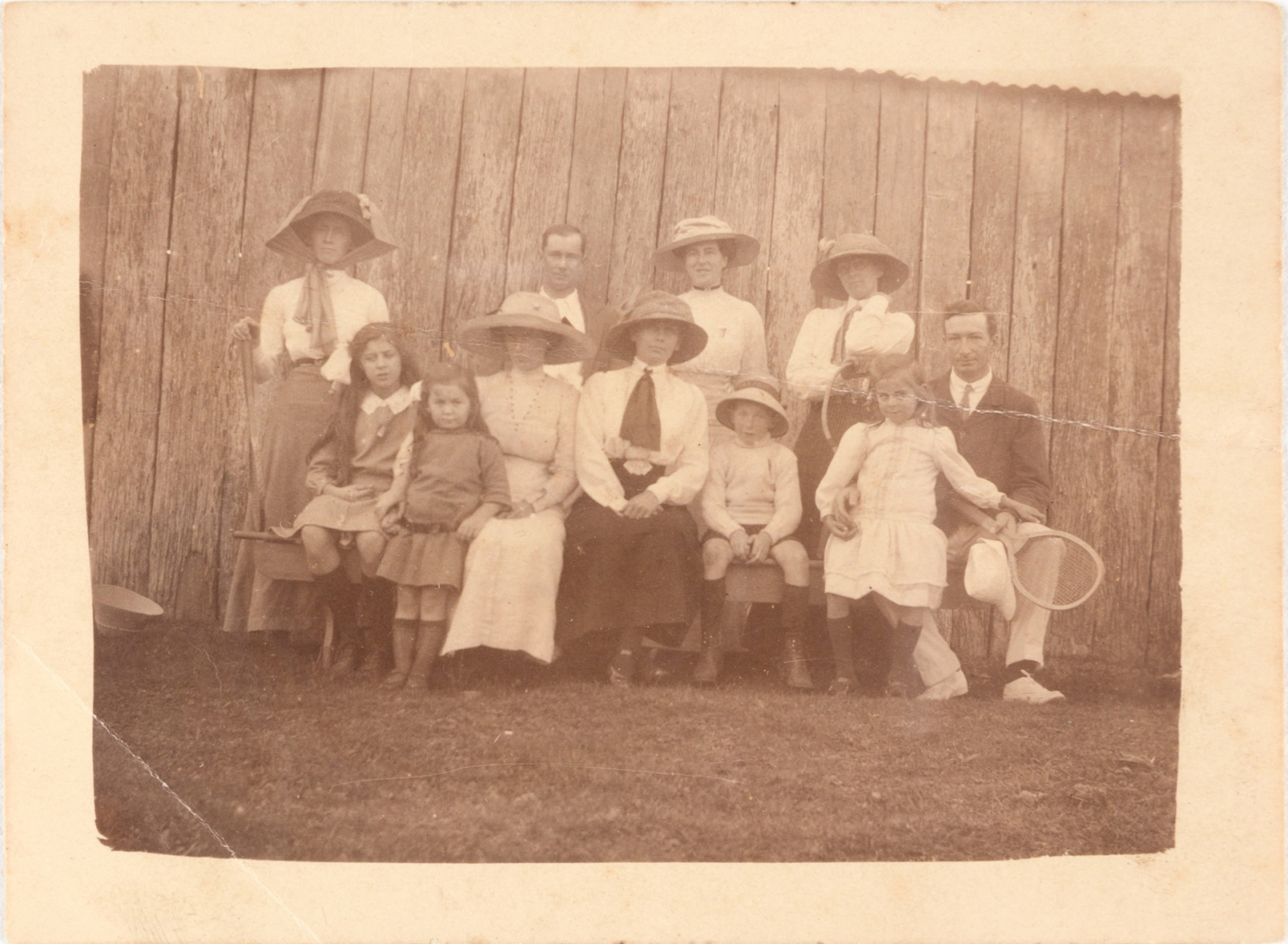 Sepia toned photo of eight people standing and seated in from of wooden building.