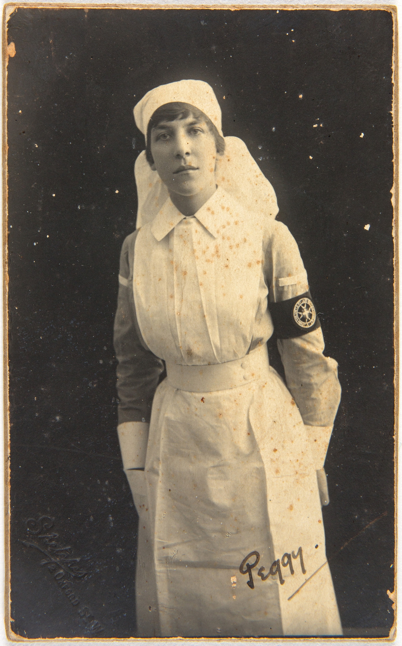 Black and white portrait of woman in nurse's uniform with armband, leaning forward.