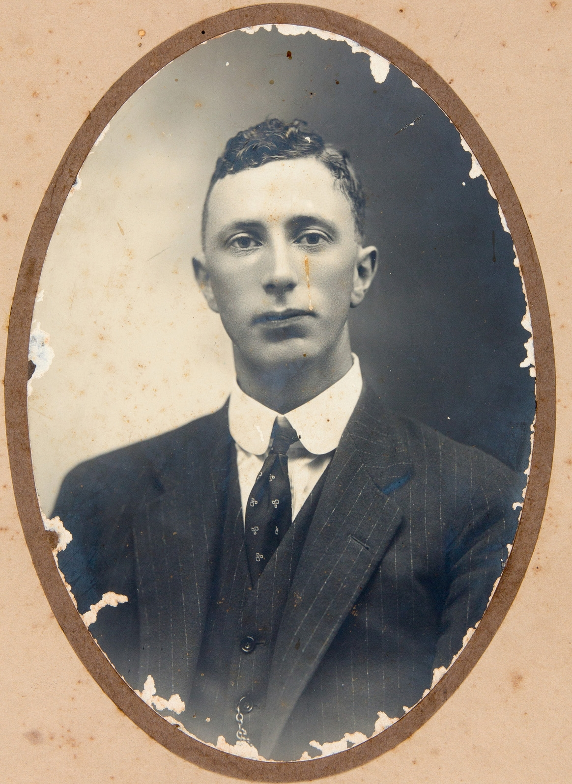 Black and white portrait in oval frame of young man in suit.