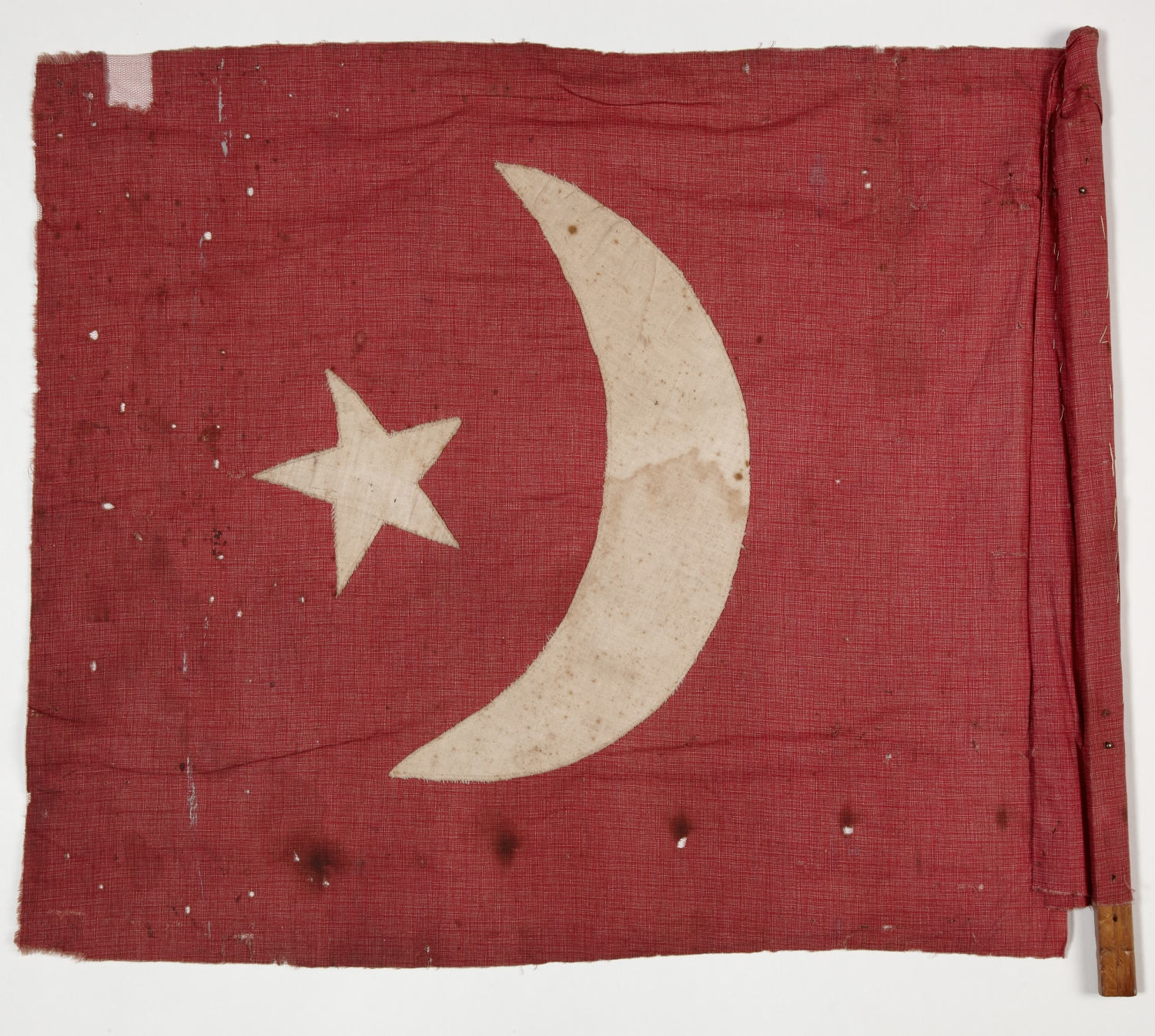 Red handmade flag with star and crescent moon sewn onto it.