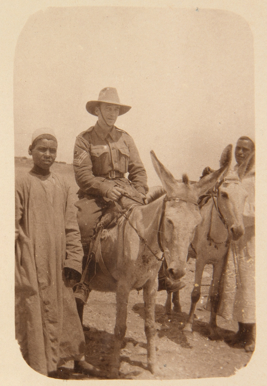 Soldier on donkey flanked by two young men.