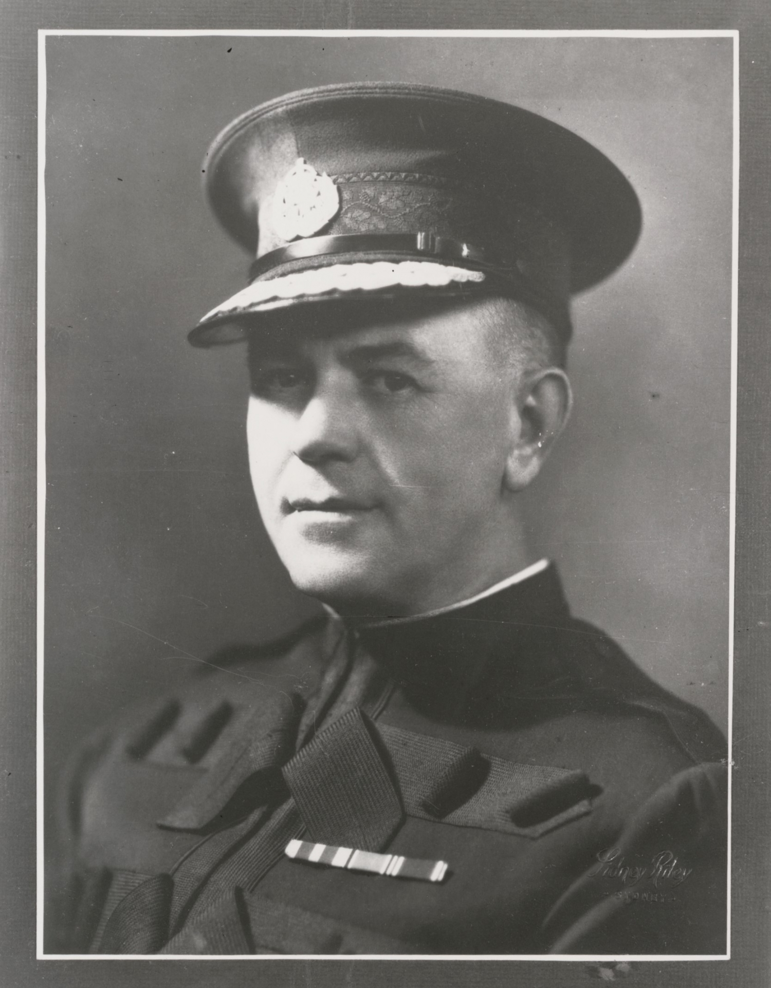Black and white portrait of man in uniform.