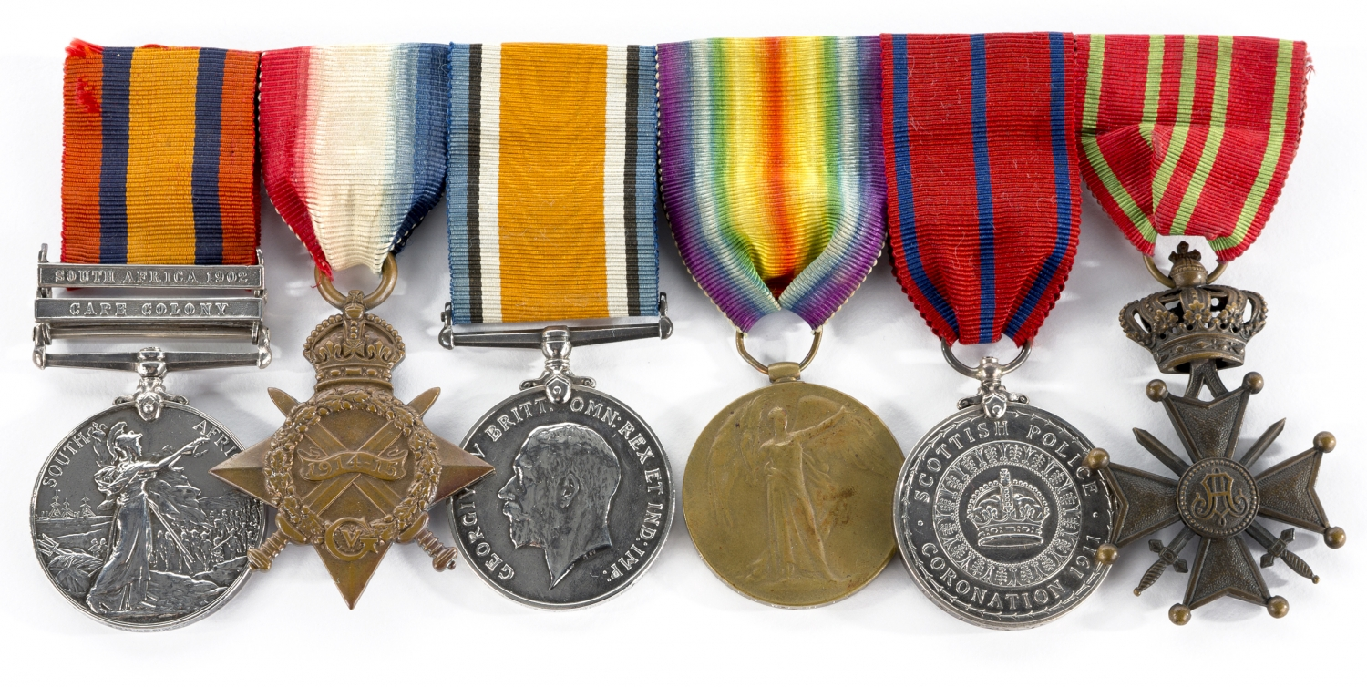 Row of six round or star-shaped medals hanging from multicoloured ribbons.