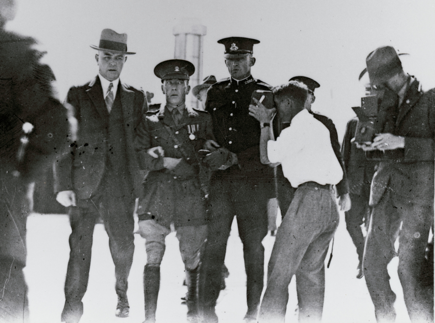 Slightly faded around edges, a black and white photo of police holding man in uniform, with photographer in action taking photos to right.