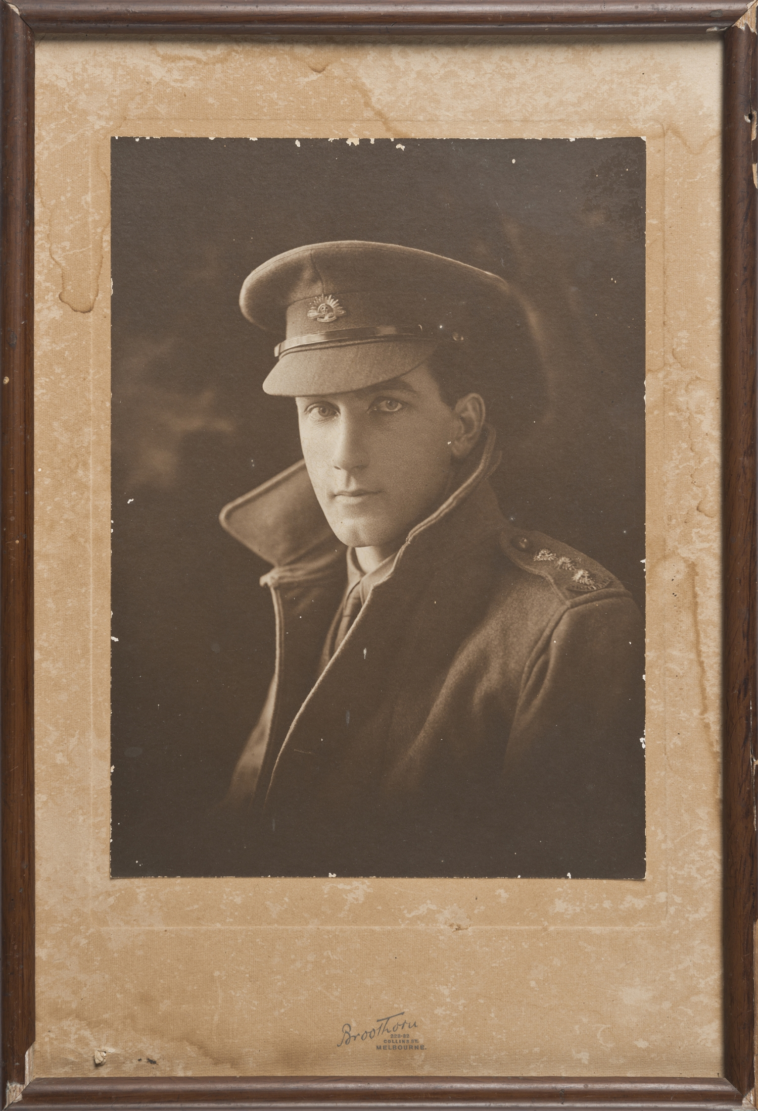 Framed sepia toned photograph of man in uniform.