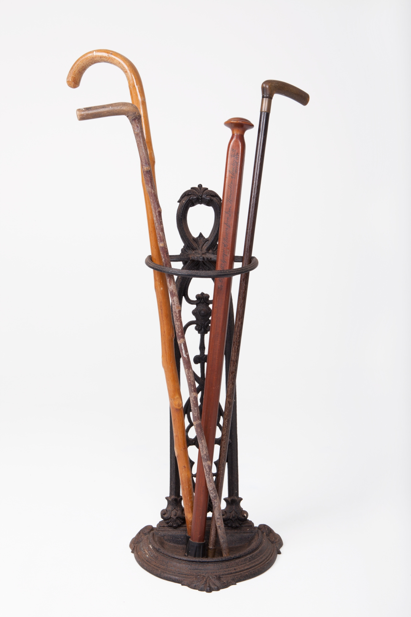Four wooden walking sticks in cast iron umbrella stand.
