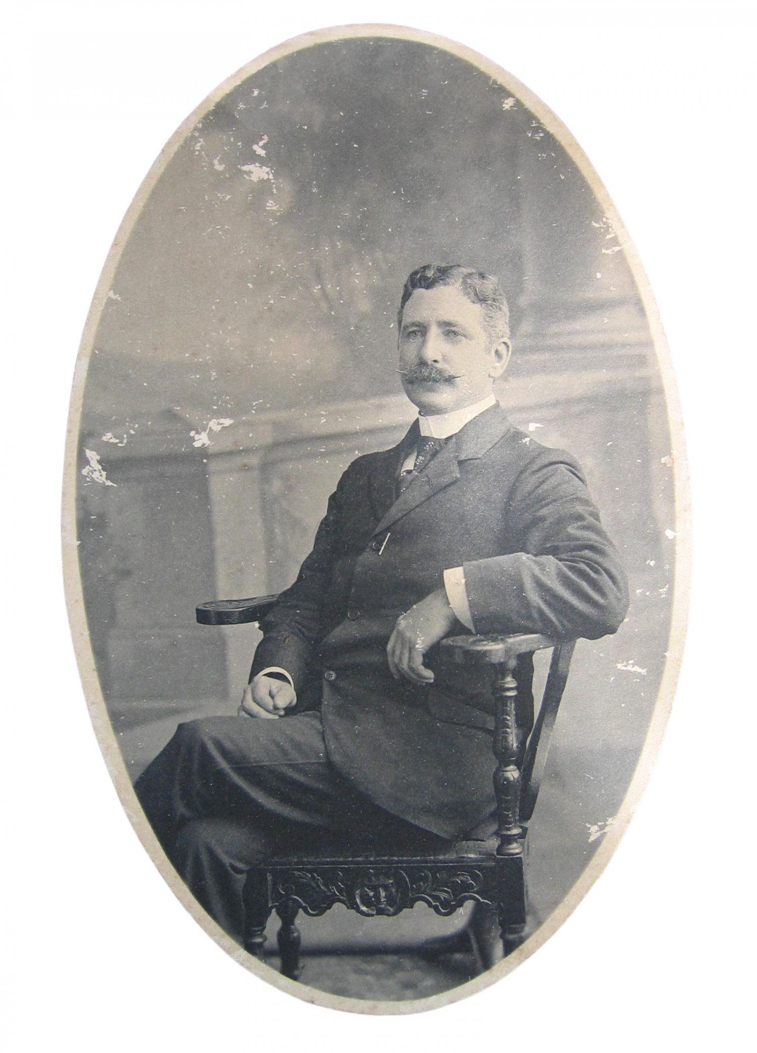 Cameo portrait of man seated in wooden armed chair.
