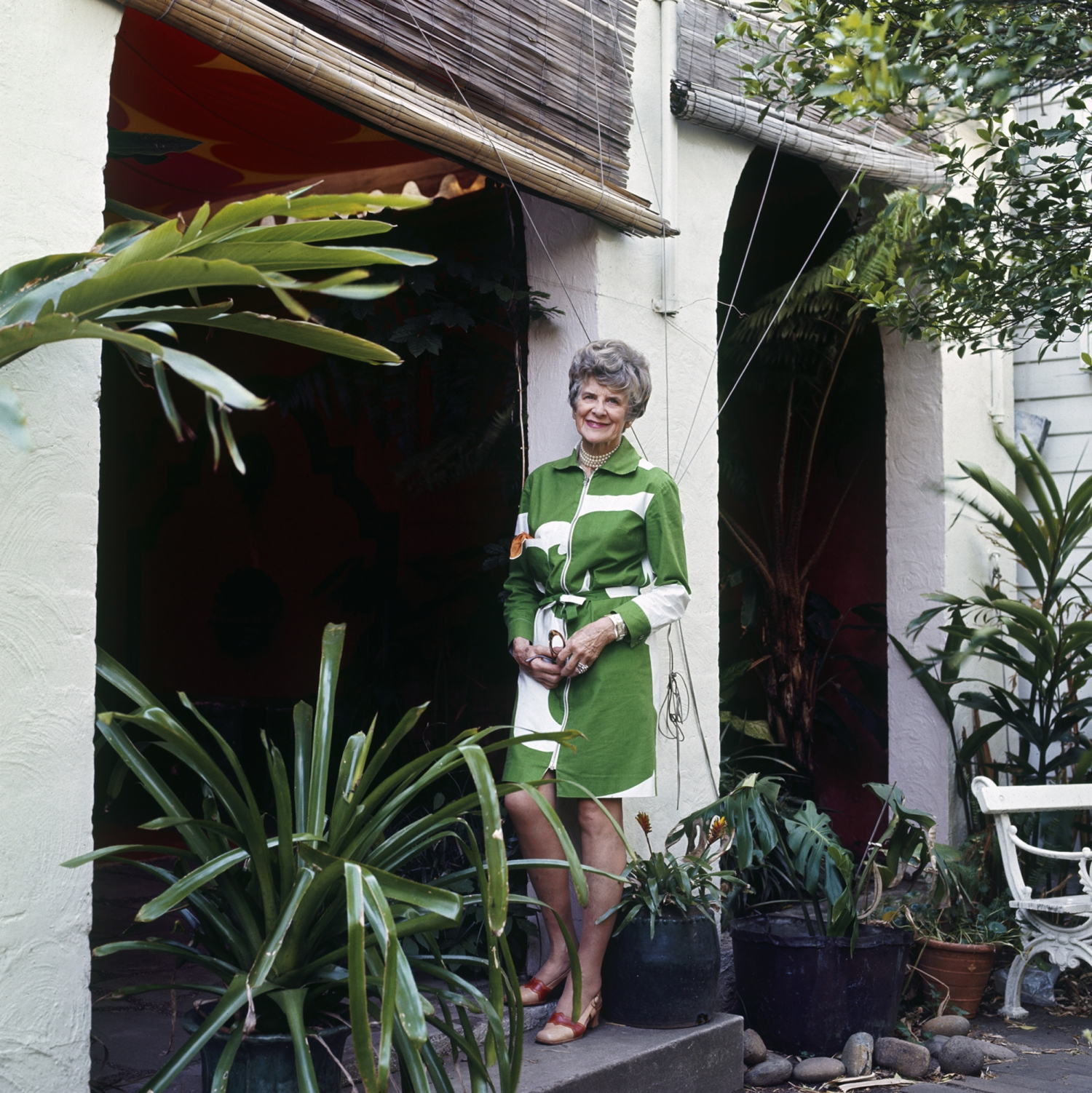 Woman in green and white patterned dress standing against white column in garden setting.
