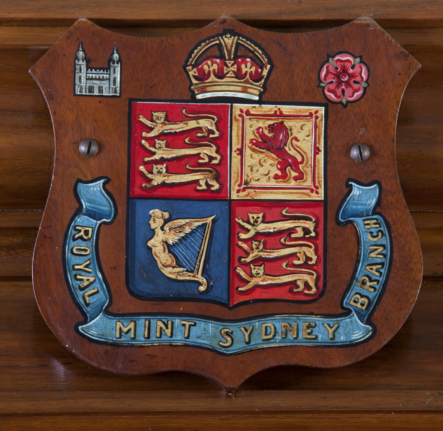 Closeup of coat of arms painted onto wood.