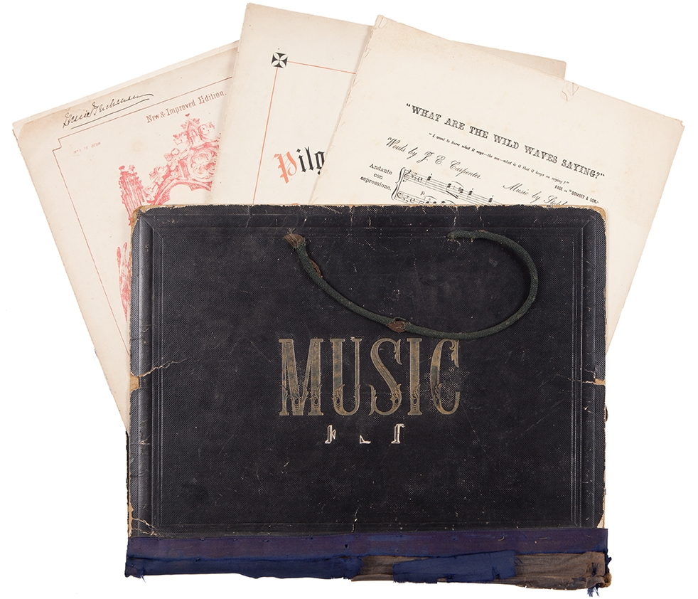Leather book with word Music embossed on front, with pages of music sticking out of top.