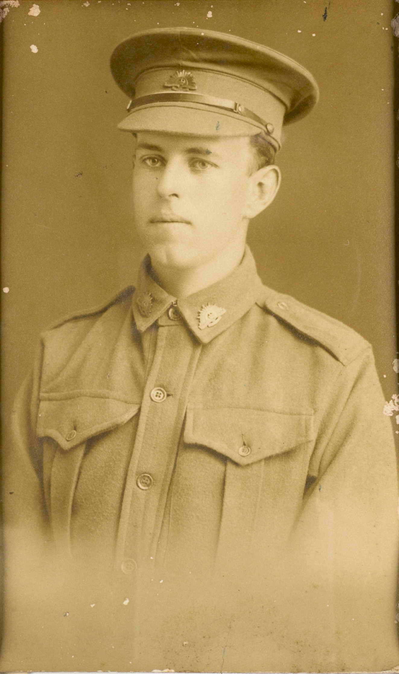 Sepia toned black and white photo of man in uniform.