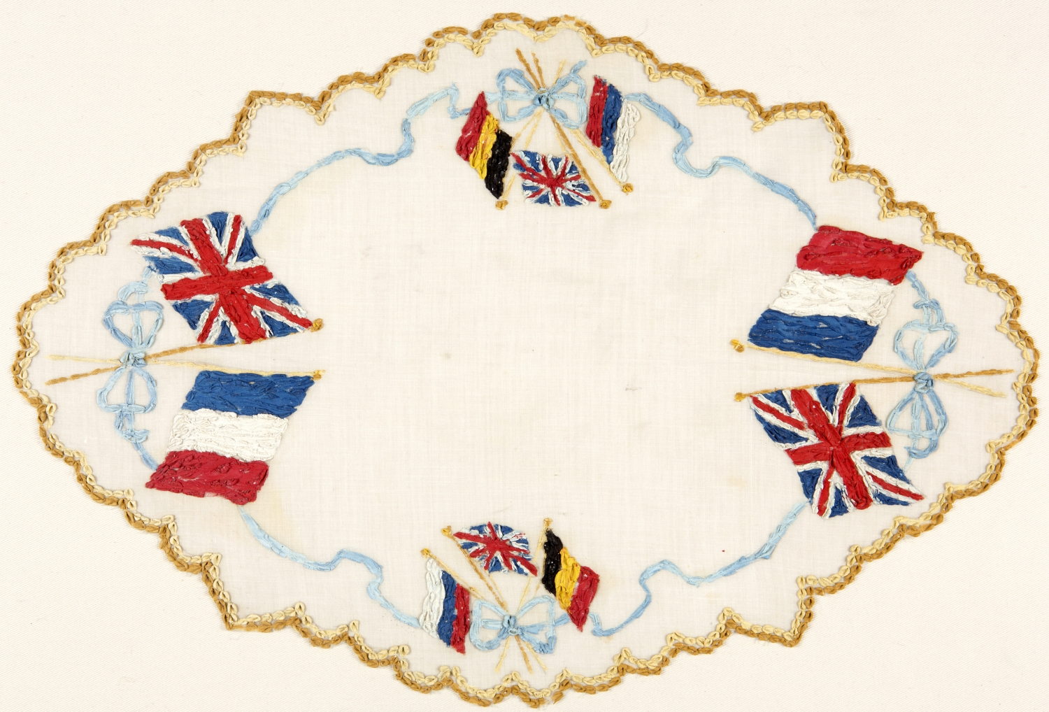 Cream doily with scalloped edge and hand painted with flag designs.
