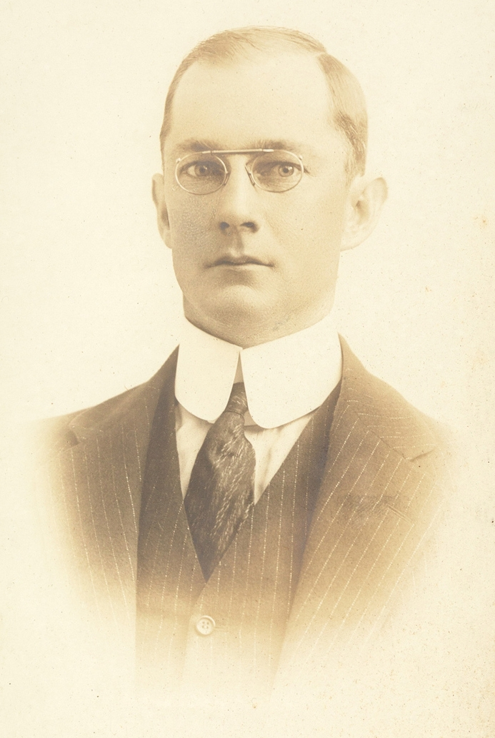 Sepia toned photo of man wearing glasses with a coat, high collar and tie.
