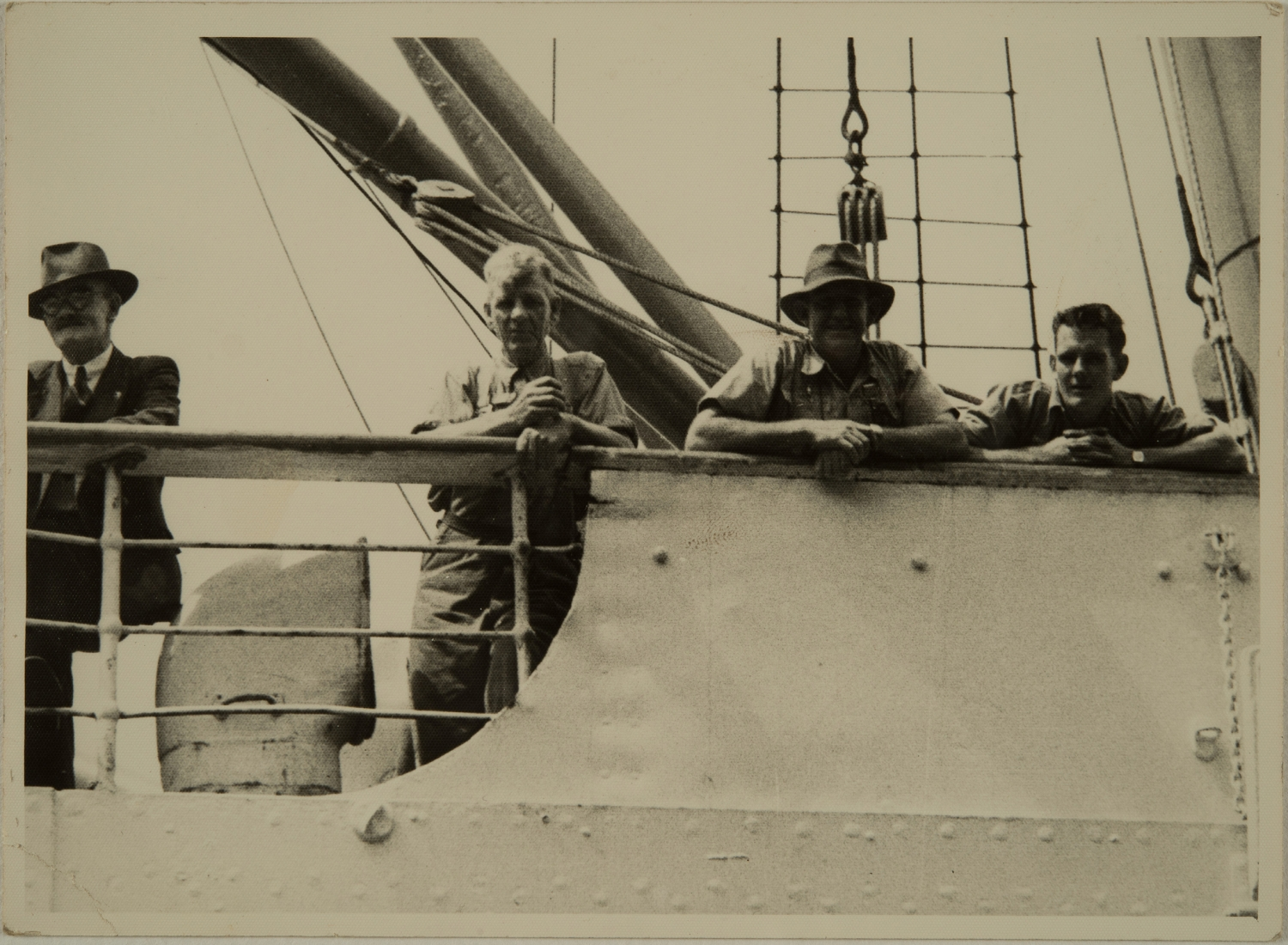 Black and white photograph depicting four men on the deck of a boat. The photograph is visible through a rectangular shaped reveal.