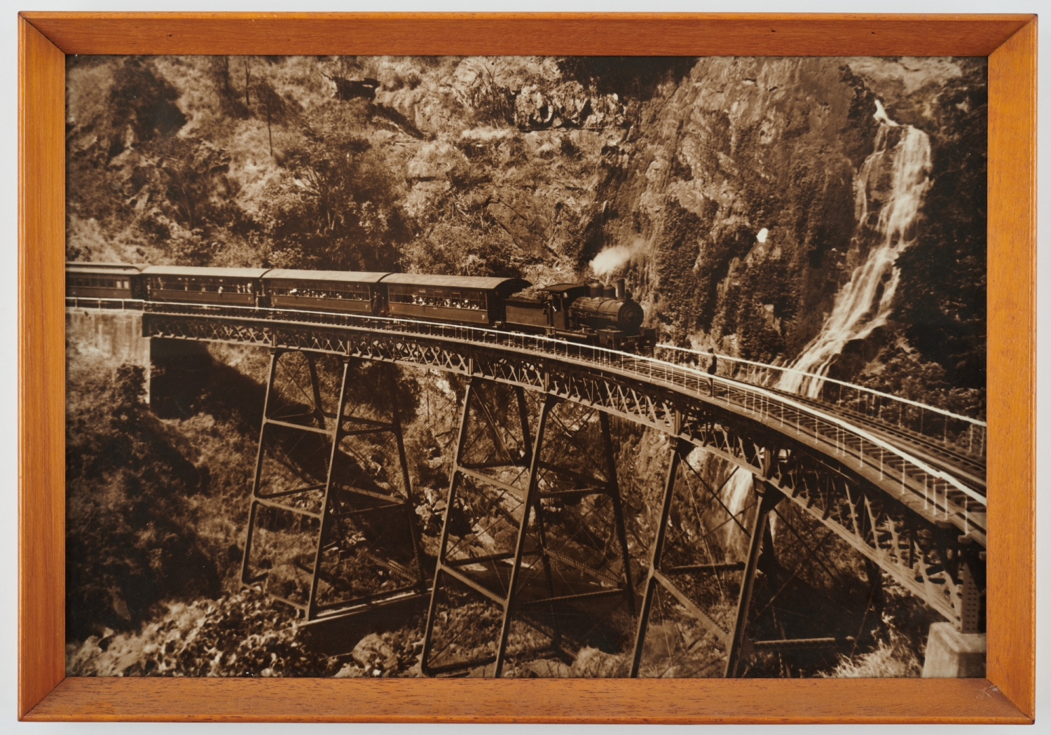 Black and white photoof railway line with steam train in brown frame.