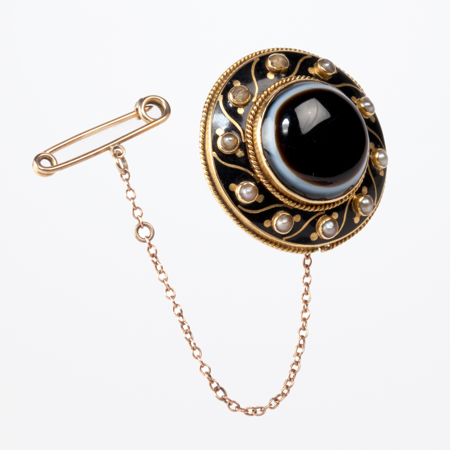 A circular gold and black enamel brooch set with central dark banded onyx and eleven seed pearls around circumference.