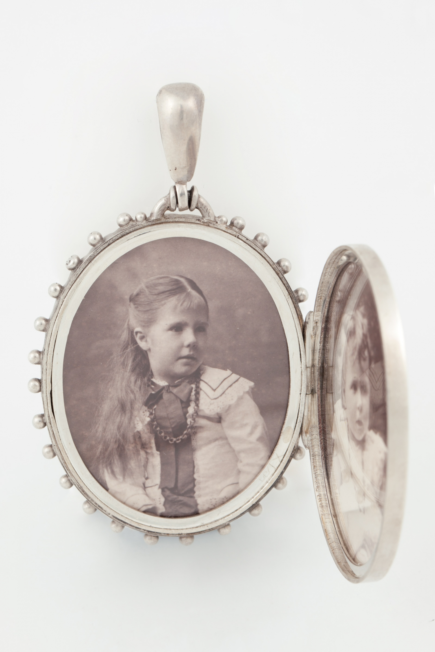 Oval silver locket containing silver gelatin portrait prints of Nina Rouse and Kathleen Rouse, made in 1905