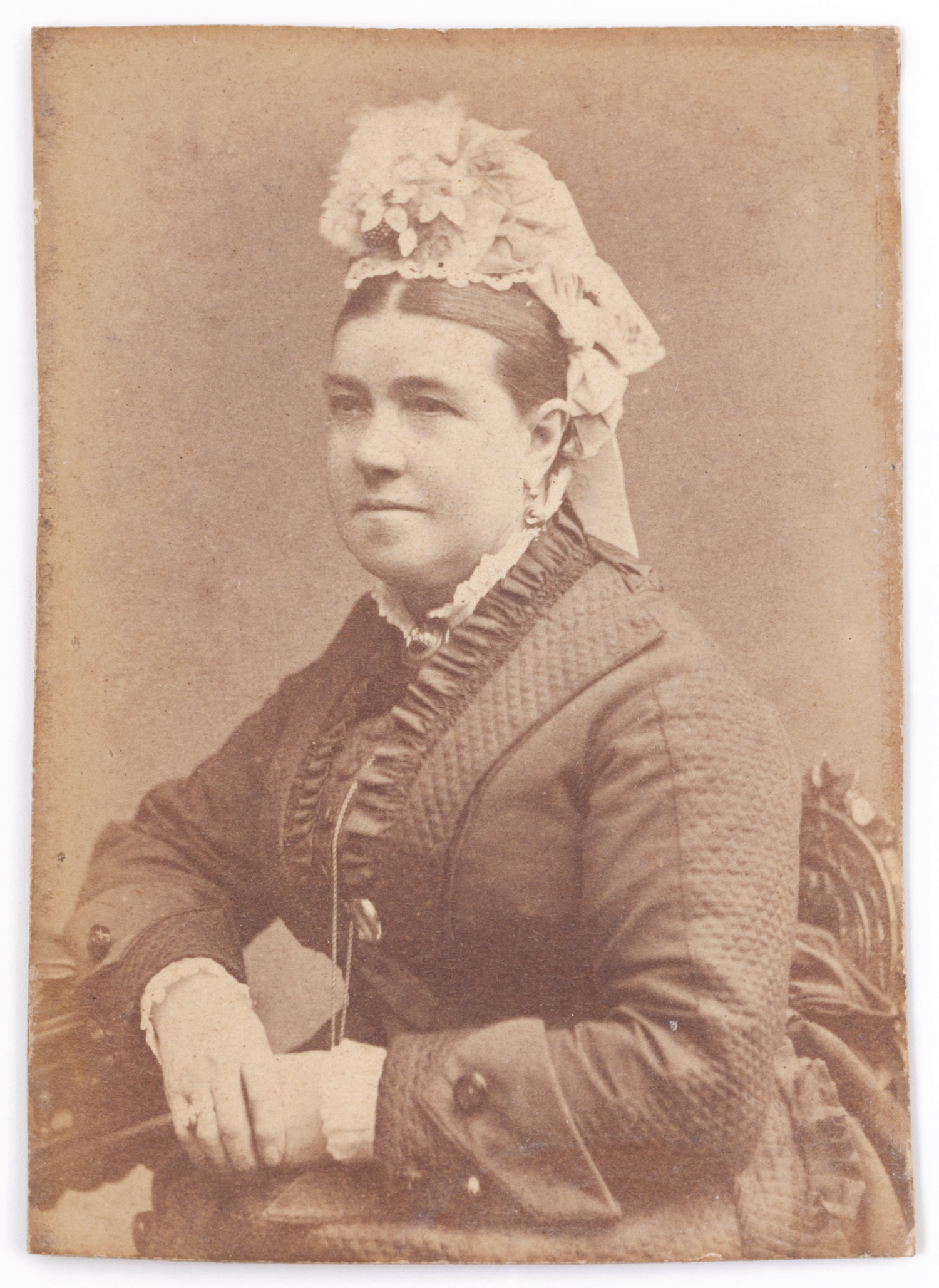 A portrait photograph of Hannah Rouse in mid Victorian costume with a long sleeved jacket with quilted sleeves and lapels and a frill down the front. Her hair is parted severely down the centre and she wears an elaborate lace cap topped with ribbons and a