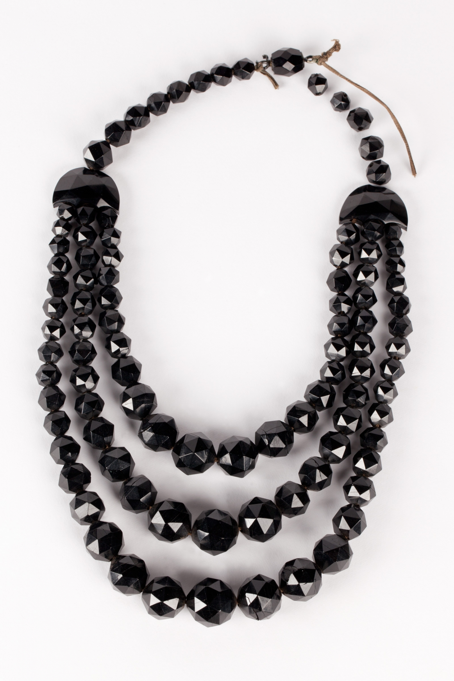 A jet necklace which consists of a single strand of faceted jet beads from which are hung three strands of graduated beads attached through faceted half-moon shaped beads.