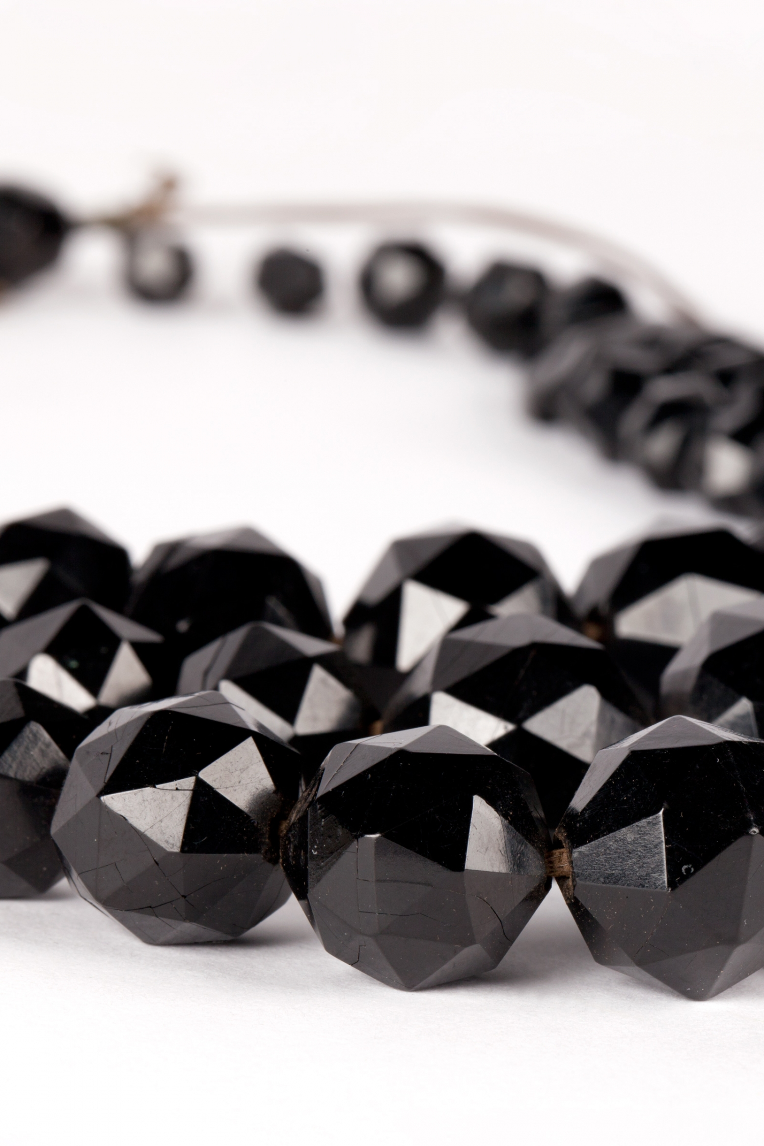 Detail view of a jet necklace which consists of a single strand of faceted jet beads from which are hung three strands of graduated beads attached through faceted half-moon shaped beads