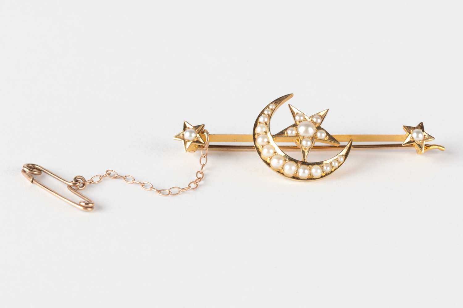 A gold bar brooch with a star and crescent moon design set with pearls. Made by Hardy Bros, Sydney, circa 1886