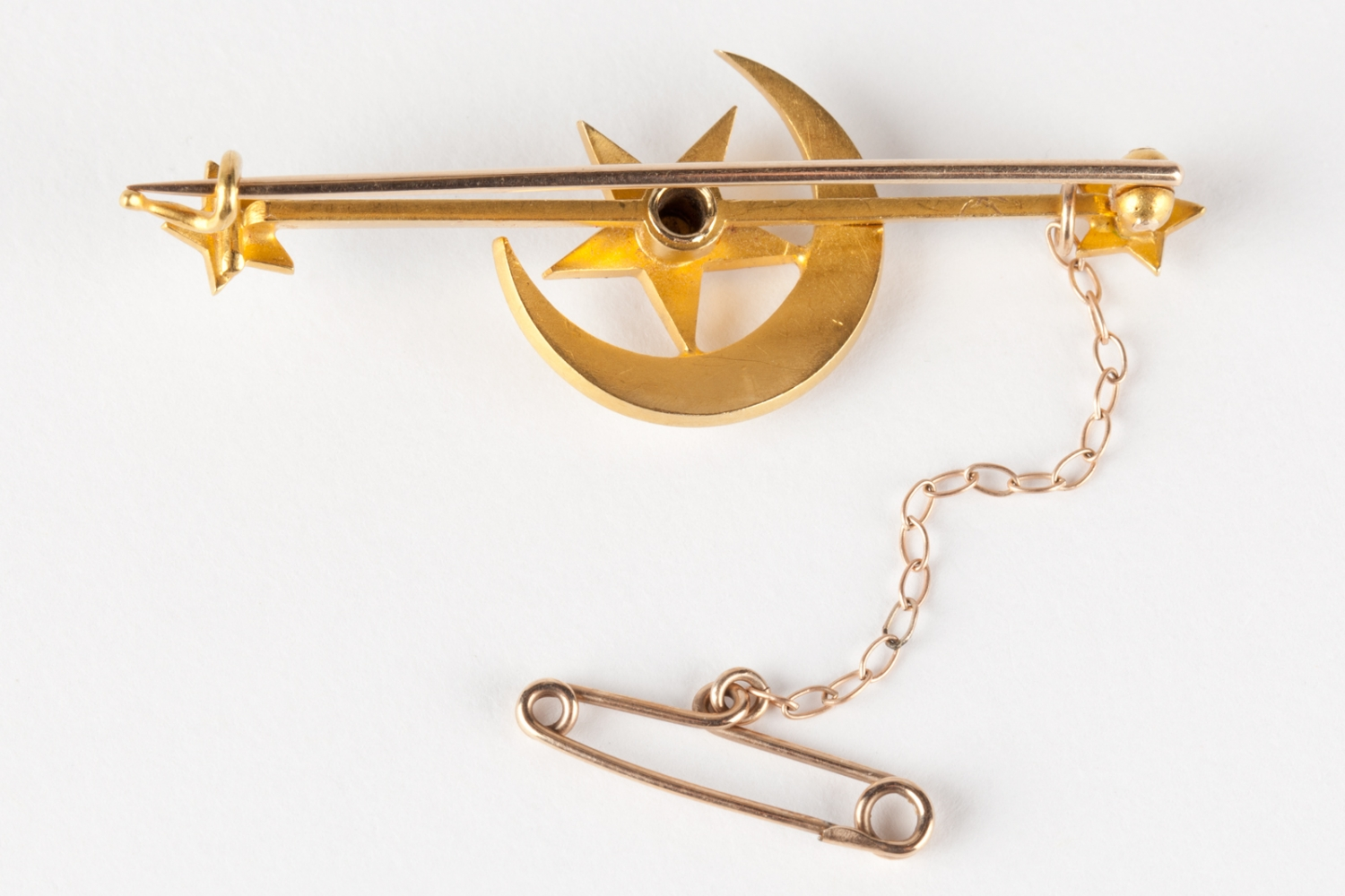 A gold bar brooch with a star and crescent moon design set with pearls. Made by Hardy Bros, Sydney, circa 1886.