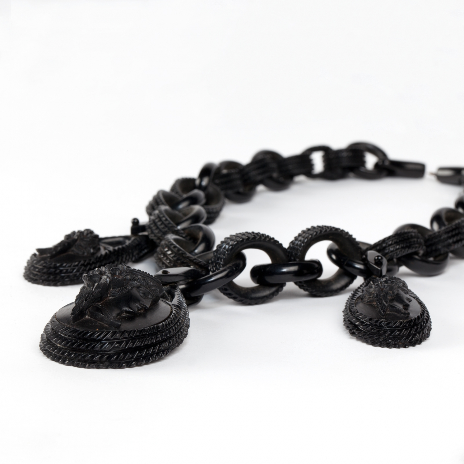 Detail view of pendants on a vulcanite necklace. The necklace is composed of 32 graduating oval links and three oval pendants.
