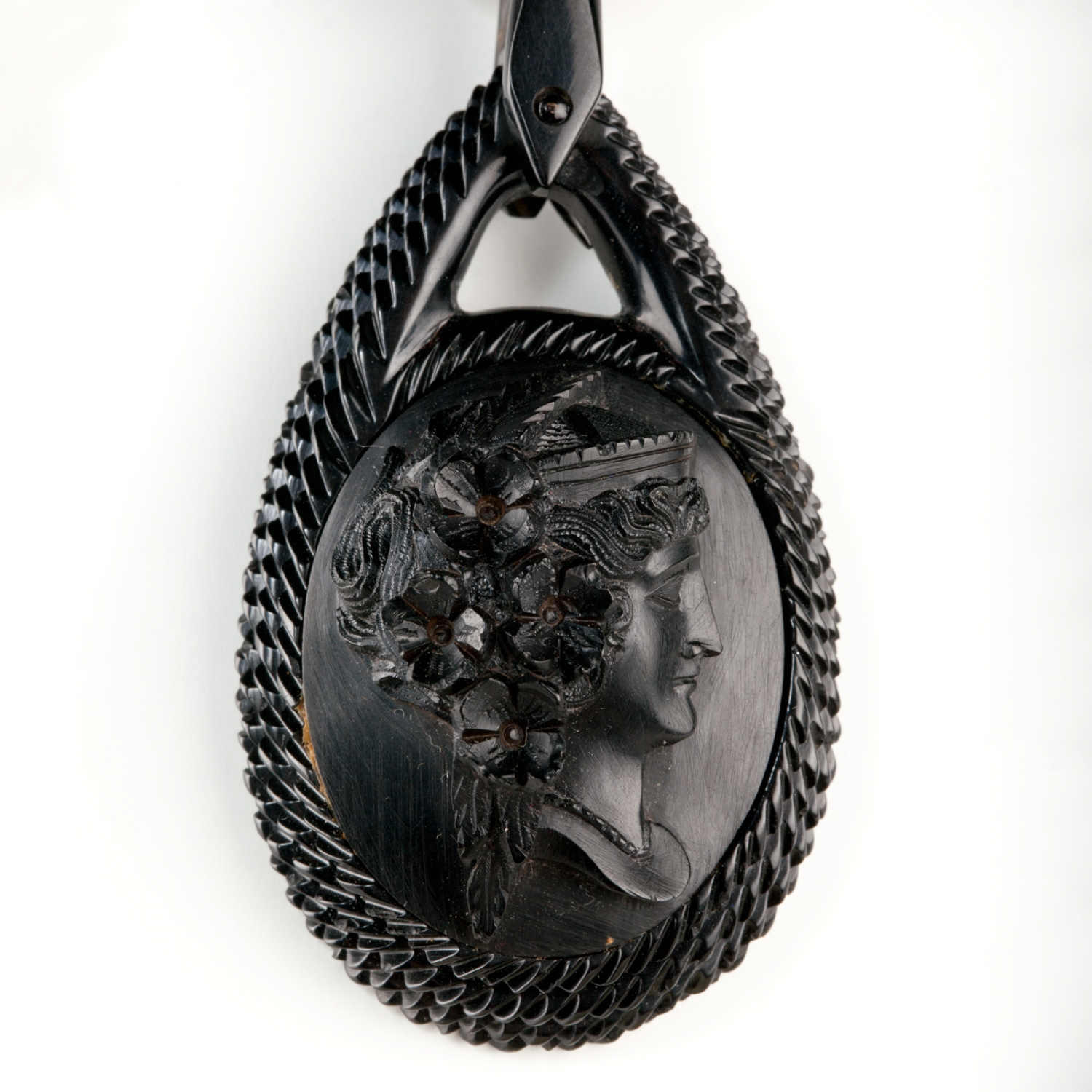 Detail view of pendant on a vulcanite necklace. The necklace is composed of 32 graduating oval links and three oval pendants.