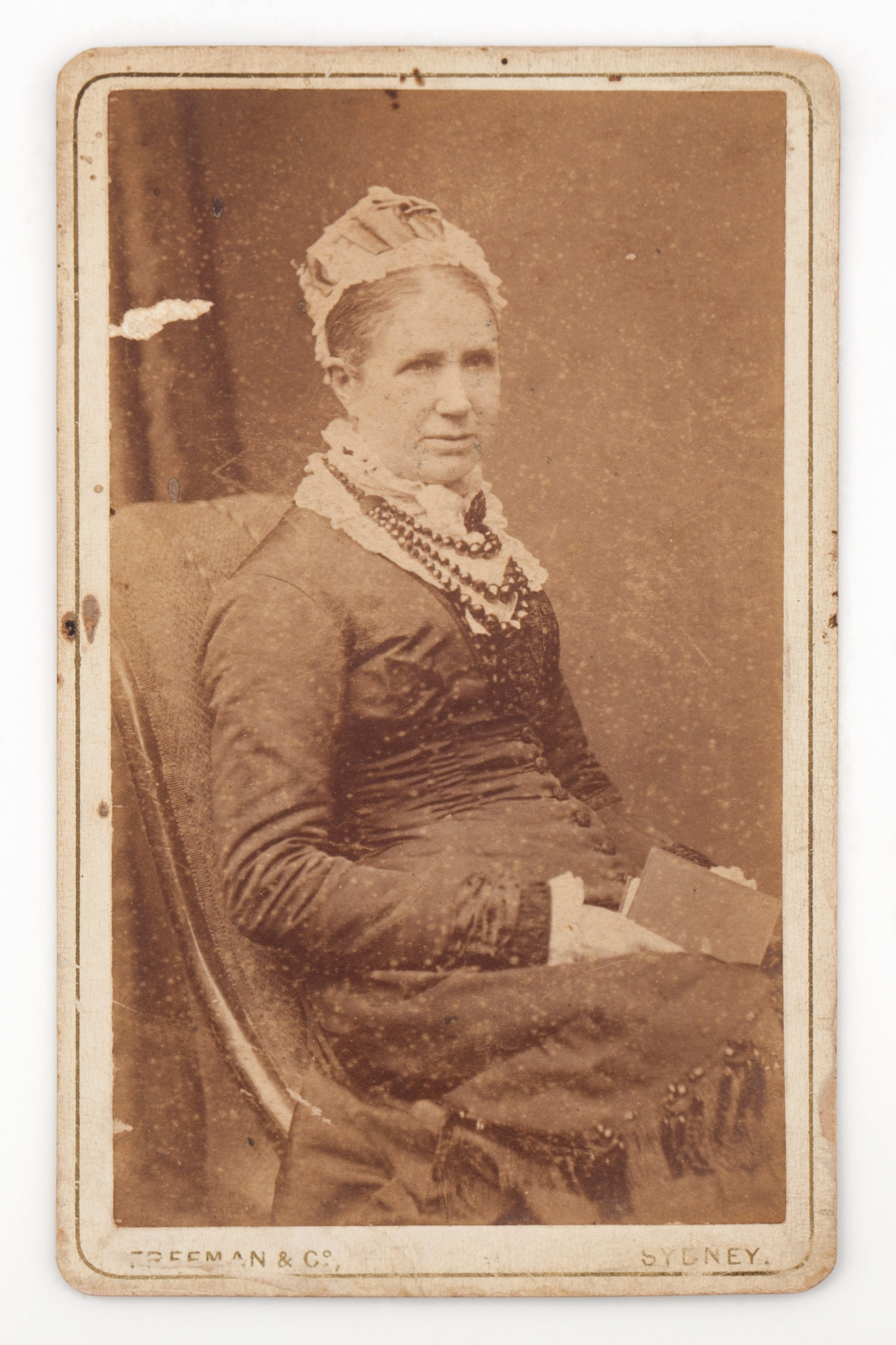 A sepia carte de visite of Elizabeth Buchanan wearing a dark coloured dress trimmed with buttons and a lace neck.