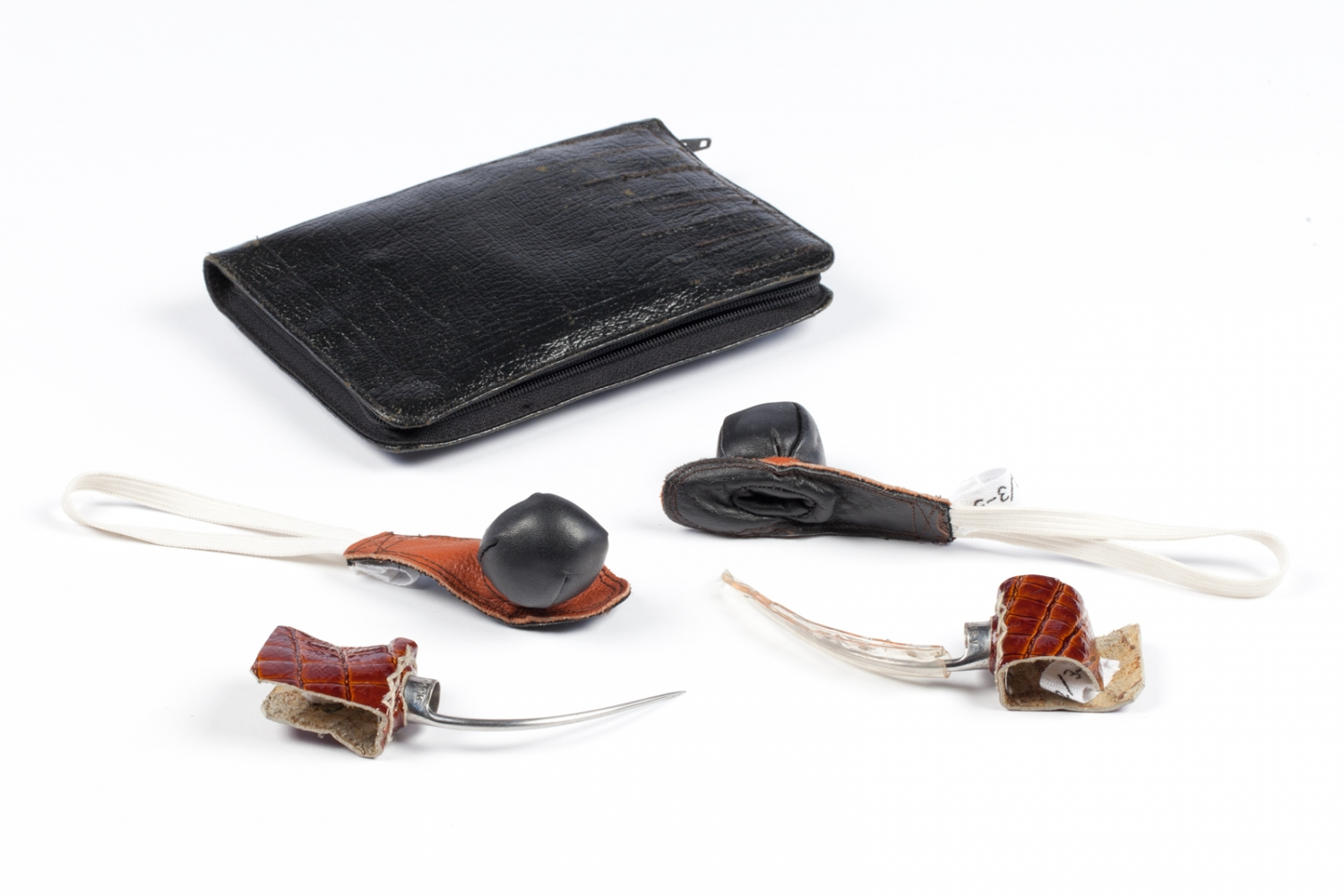 Black leather wallet containing cock fighting spurs and pads, date unknown