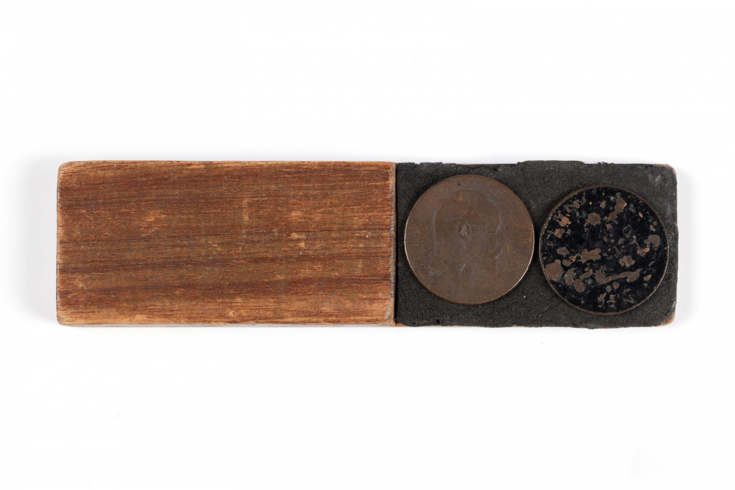 Two up game pieces consisting of a wooden 'kip' and two Australian pennies, date unknown