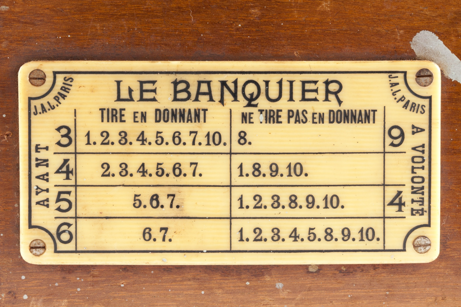 Yellow plastic label on a wooden card shoe (detail), early 20th century