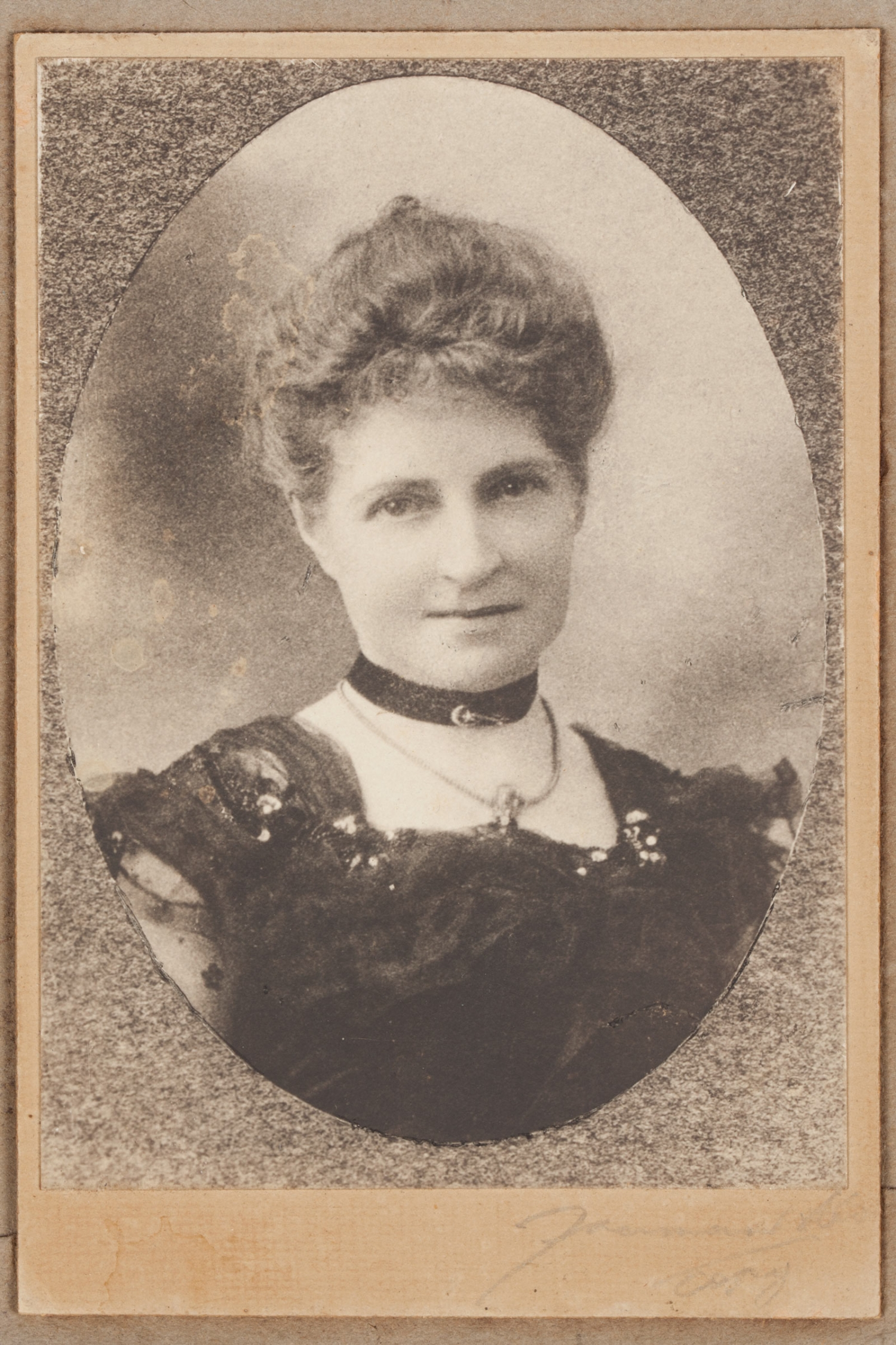 A head and shoulders portrait photograph of a woman, Bessie Rouse, wearing a dress with a square neckline and a black velvet at her neck decorated with a gold bar brooch