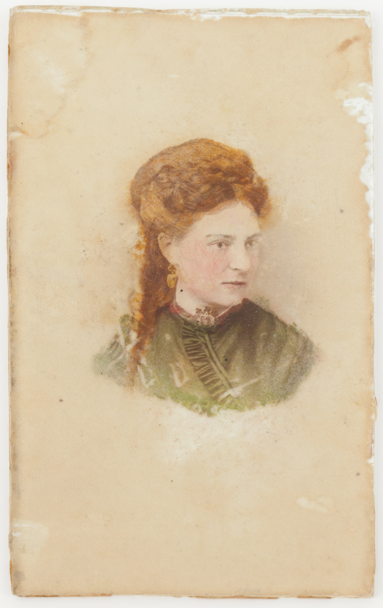 A photograph, hand-coloured using the crystoleum process, depicts a radiantly red-haired young woman, dressed in green