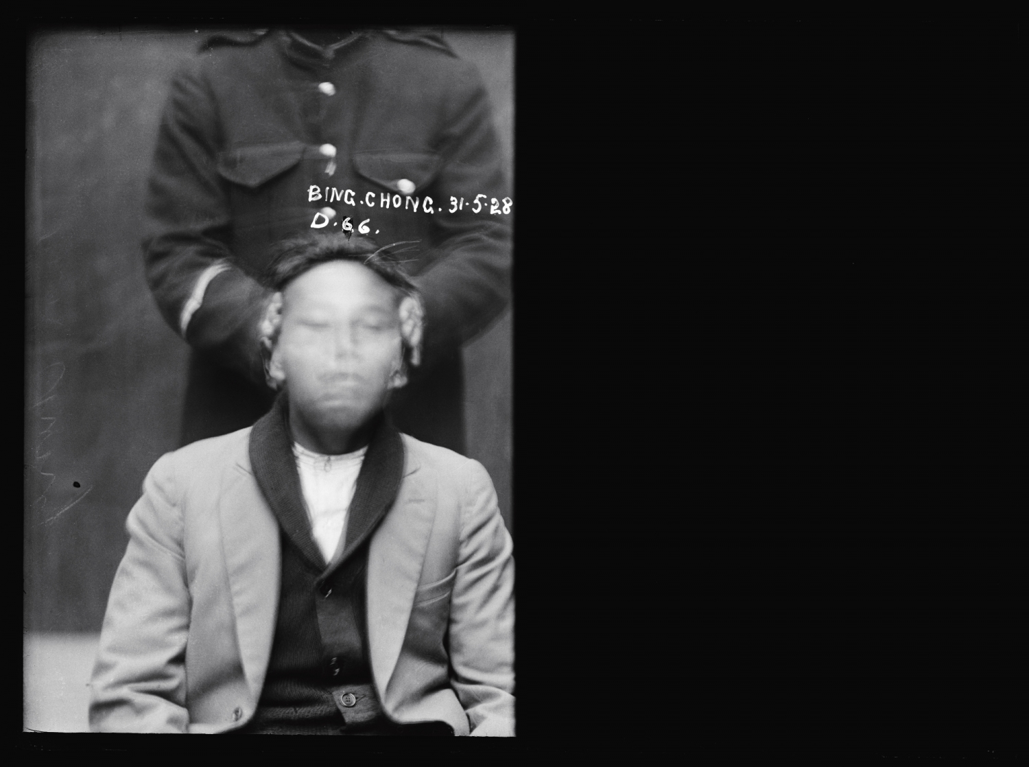 Half of dual mugshot showing blurred face of seated man with head being held by pair of hands.