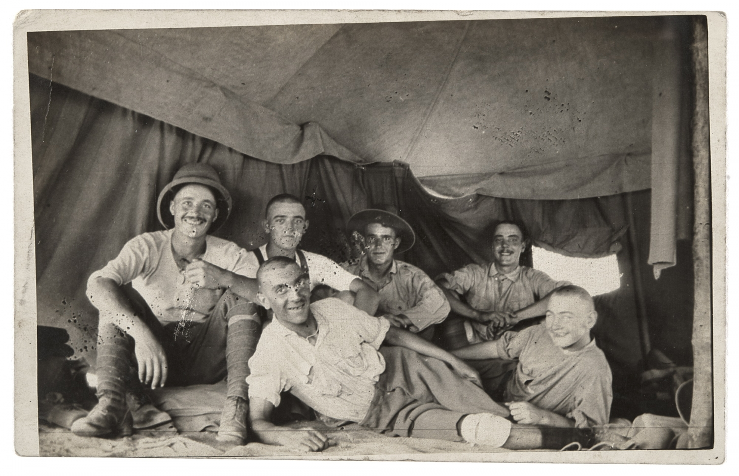 Black and white postcard photo print of five men, one reclining in front of the other four who are seated on ground.