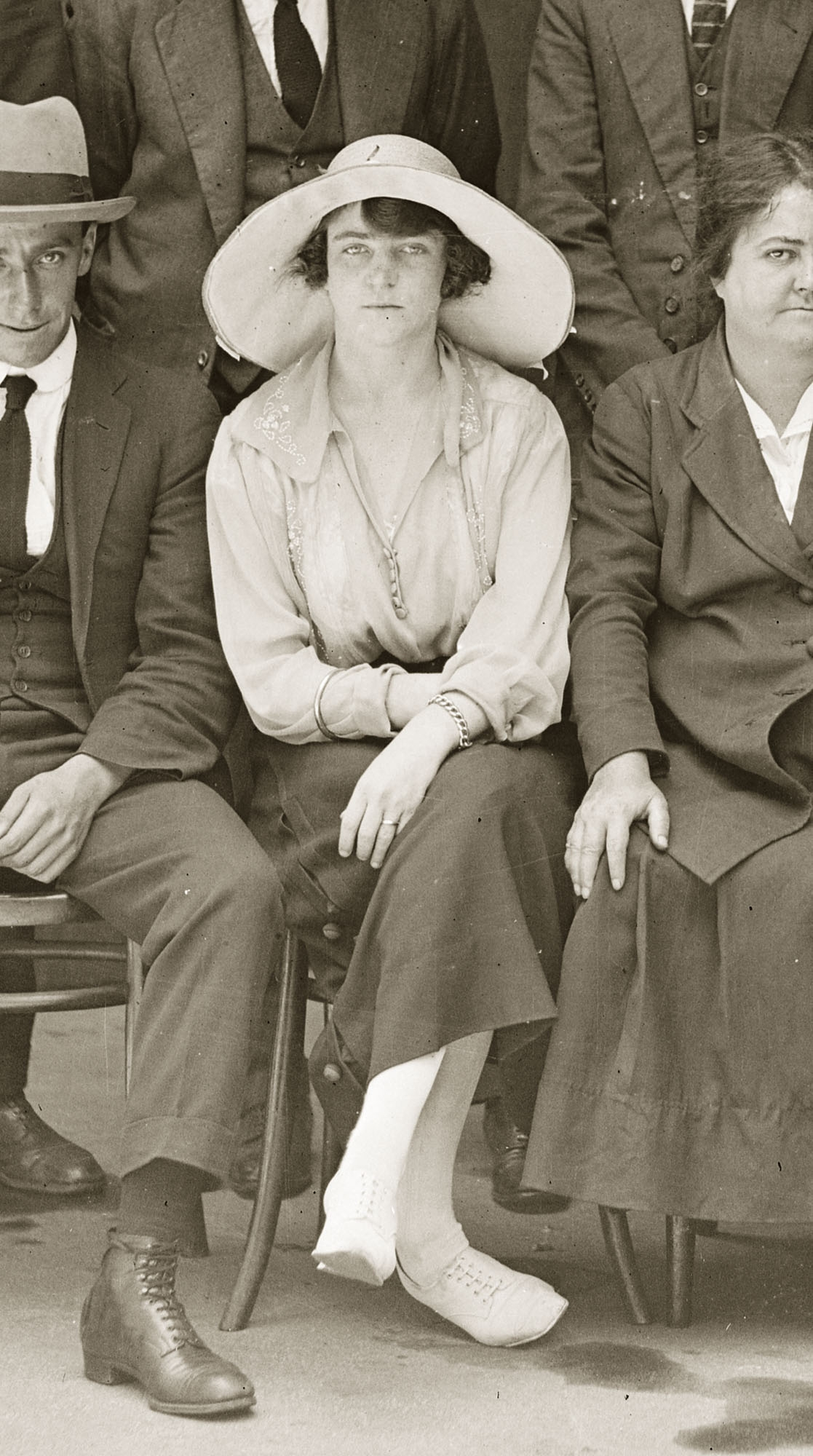 Woman in straw hat among group of seated people.
