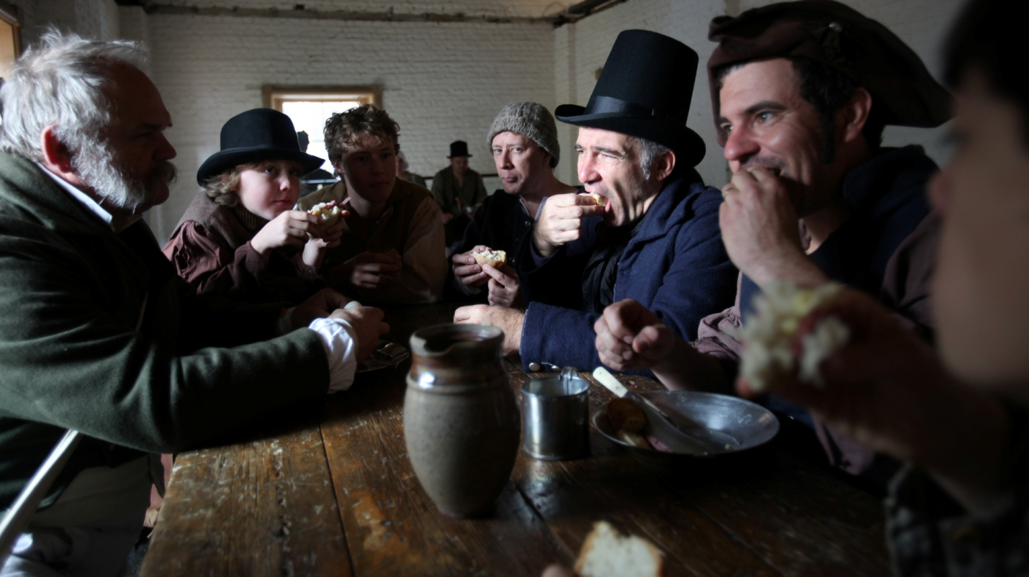 Men dressed as convicts seated at wooden table eating and drinking.