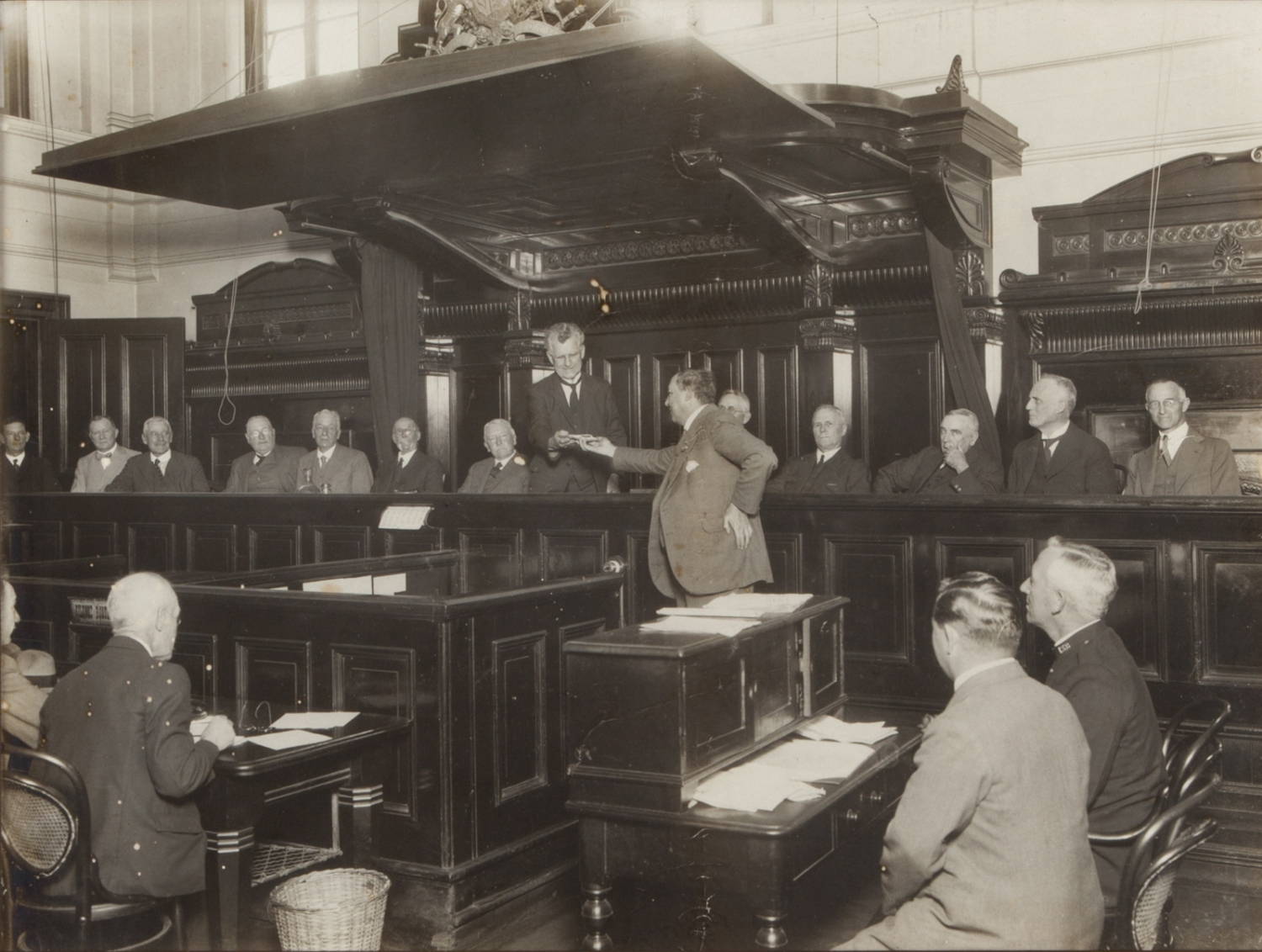 Black and white interior shot of wooden panelled courtroom filled with people.