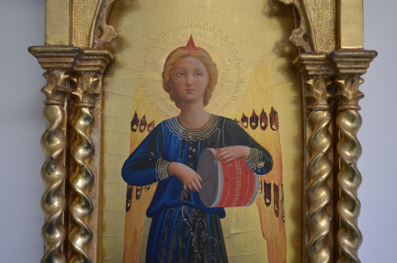 Close up of ornate gilt painting of angel's head in painting