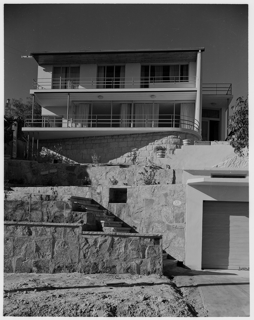 Black and white photo of multi-storeyed modernist house set above terraced garden.