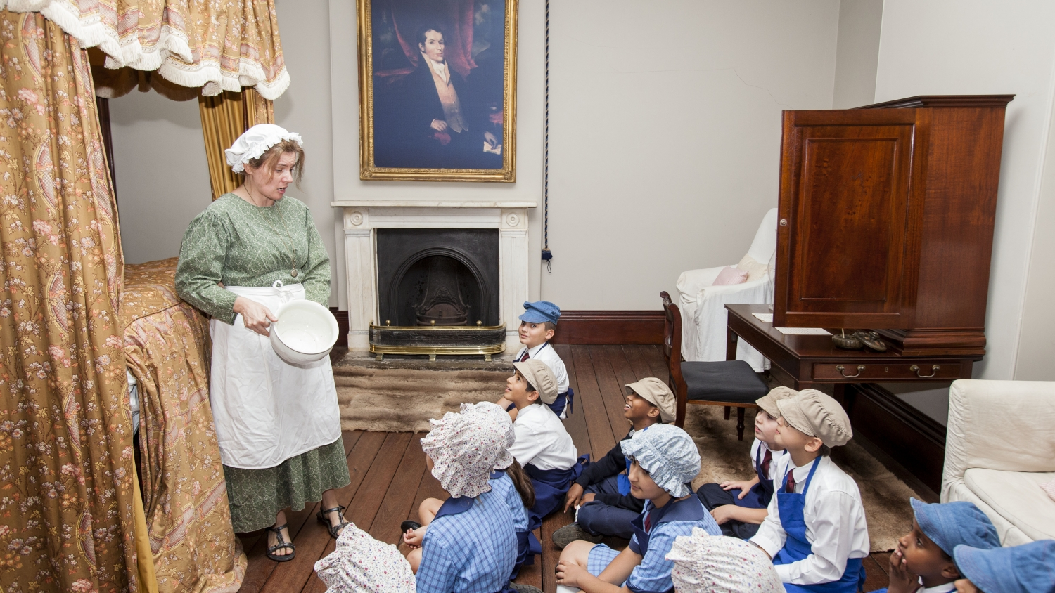 group of young student wearing costumes listening to female teacher standing in colonial period bedroom with large bed, fireplace, painting and wallaby skin rugs in the room.