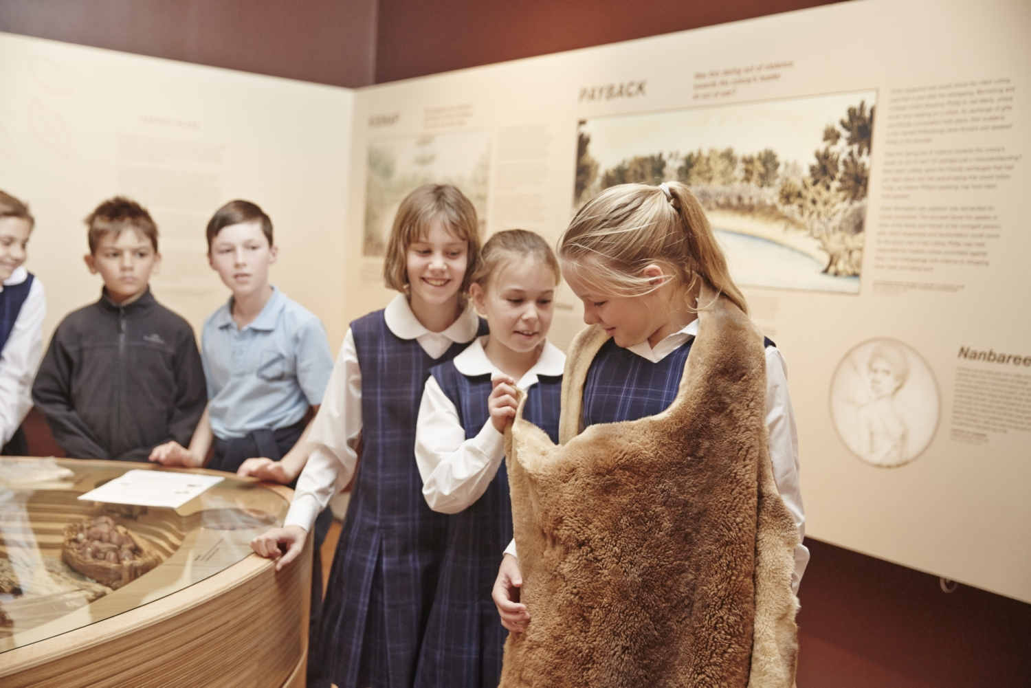 Kids in uniform trying on kangaroo skin cloak in exhibition space.