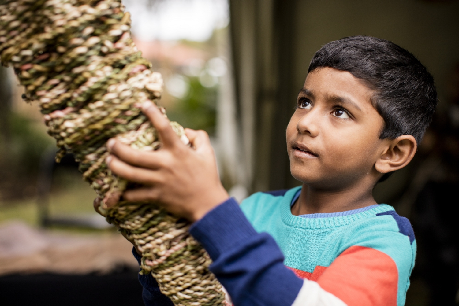 Boy holding large woven object.