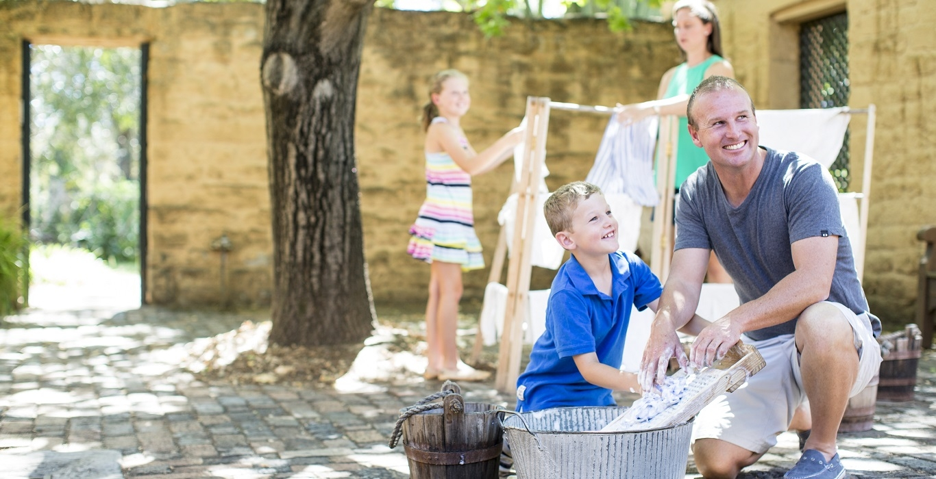 Family washing and hanging clothes in the Oak Tree Court at Elizabeth Farm