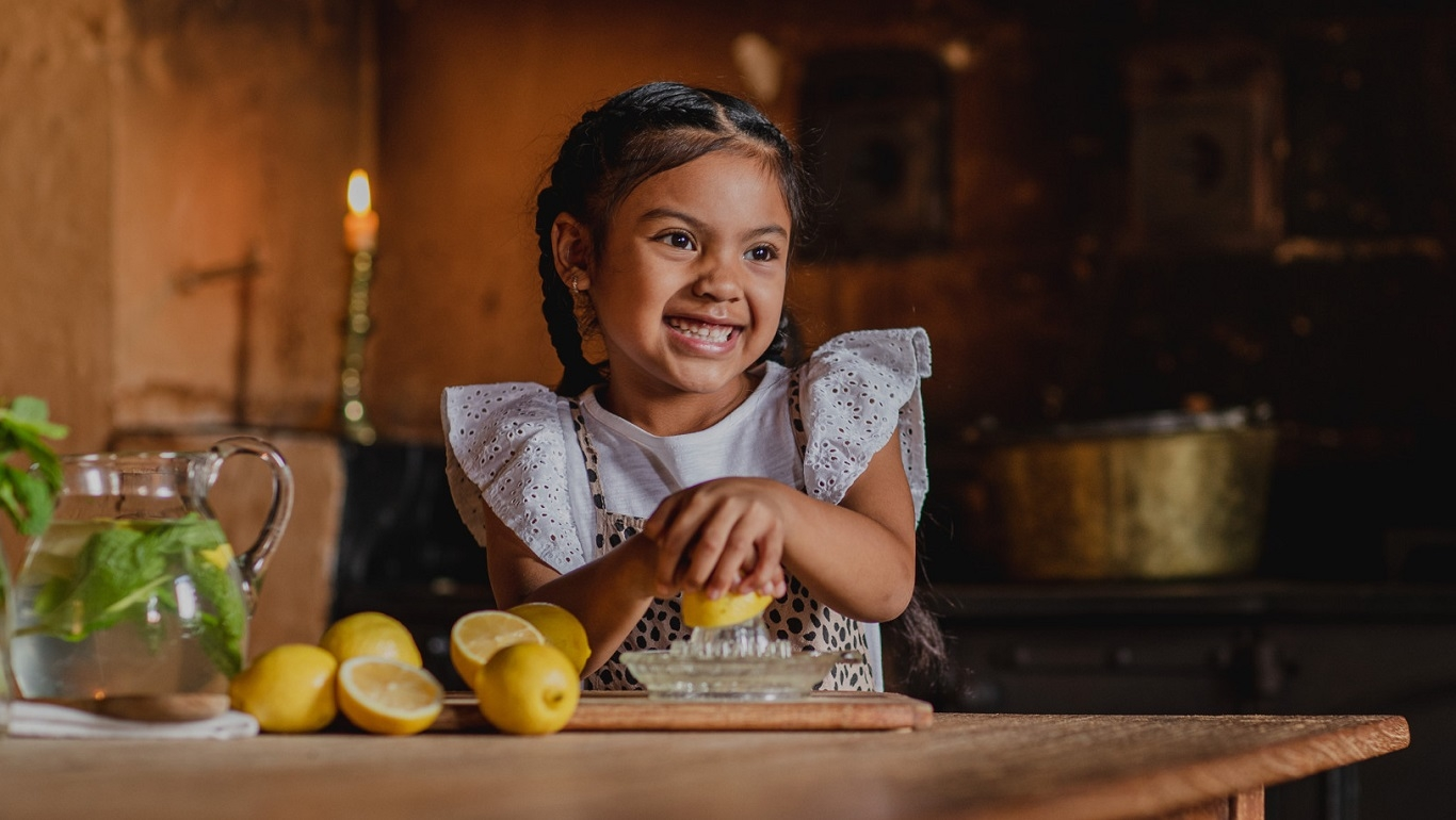 Girl squeezing lemons in kitchen