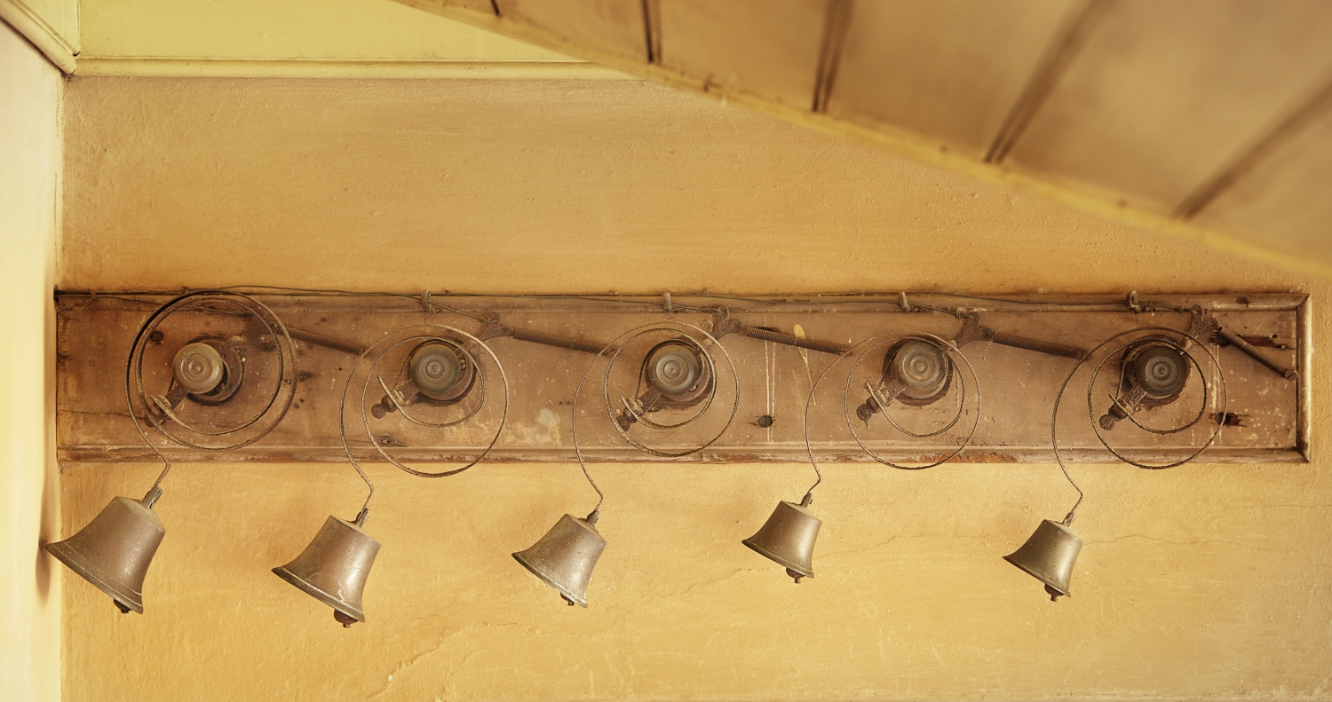 a set of brass bell mounted to a long narrow horizontal board attached to a yellow limewashed wall.