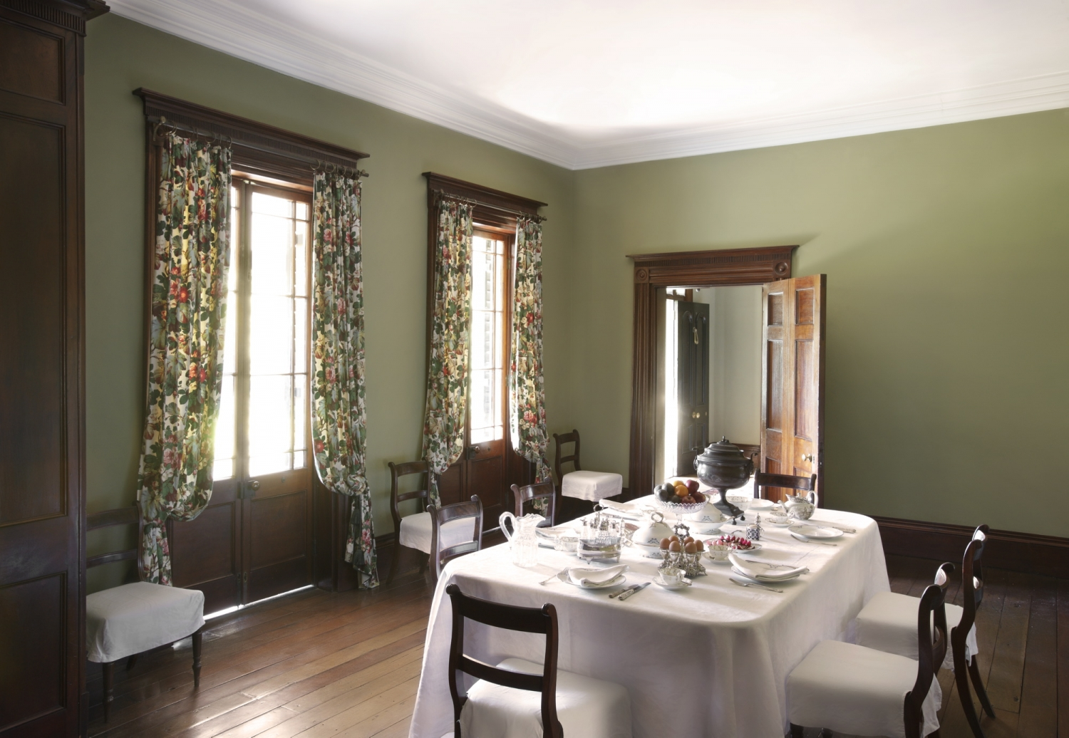 A table set for a meal with china and cutlery in a room with sunlit windows with floral curtains tied back.